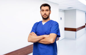 healthcare, profession and medicine concept - doctor or male nurse in blue uniform with crossed arms over hospital corridor background