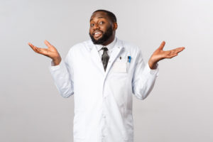 Coronavirus, covid19 and healthcare concept. Dont know cant help sorry. Portrait of reluctant, unbothered handsome african-american doctor shrugging clueless, puzzled and have no idea.