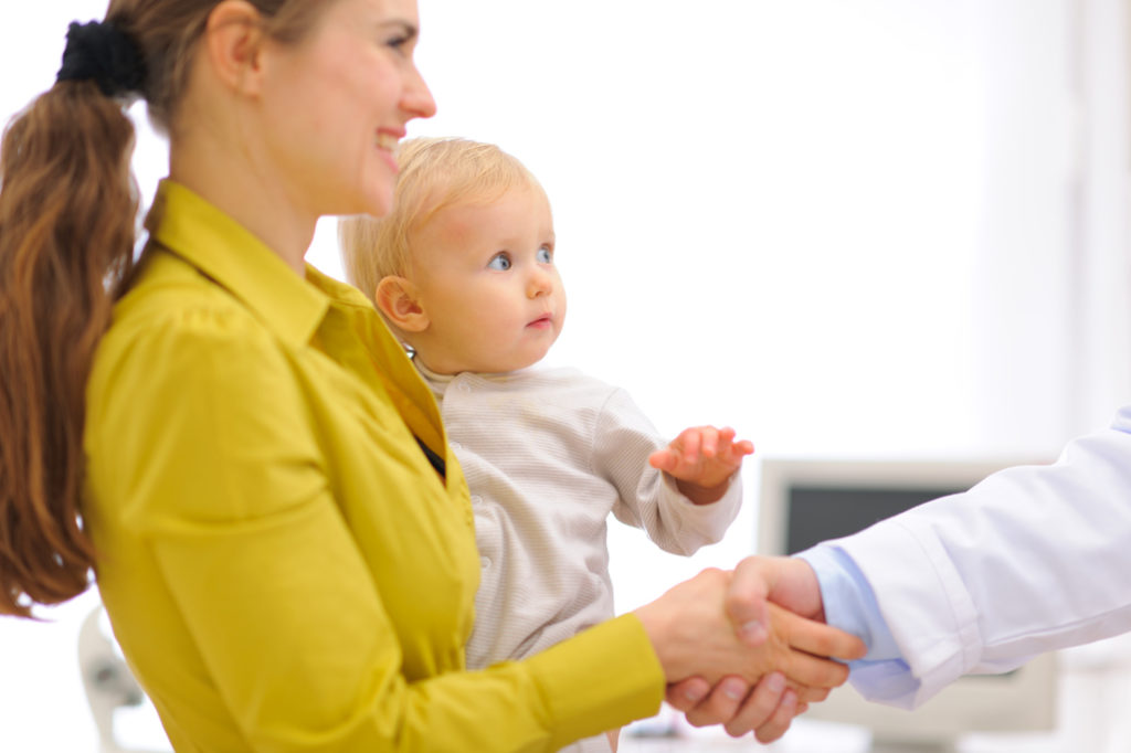Closeup on mother with baby thanking pediatrician doctor for examination
