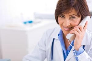 Senior female doctor calling on phone, smiling.