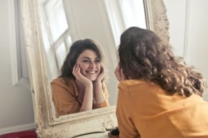 Woman looking at herself satisfactorily in the mirror