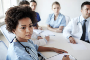 health care, profession, people and medicine concept - african american female doctor or nurse over group of medics meeting at hospital