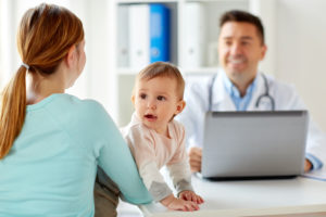 medicine, healthcare, pediatry and people concept - happy woman with baby and doctor with laptop computer at clinic